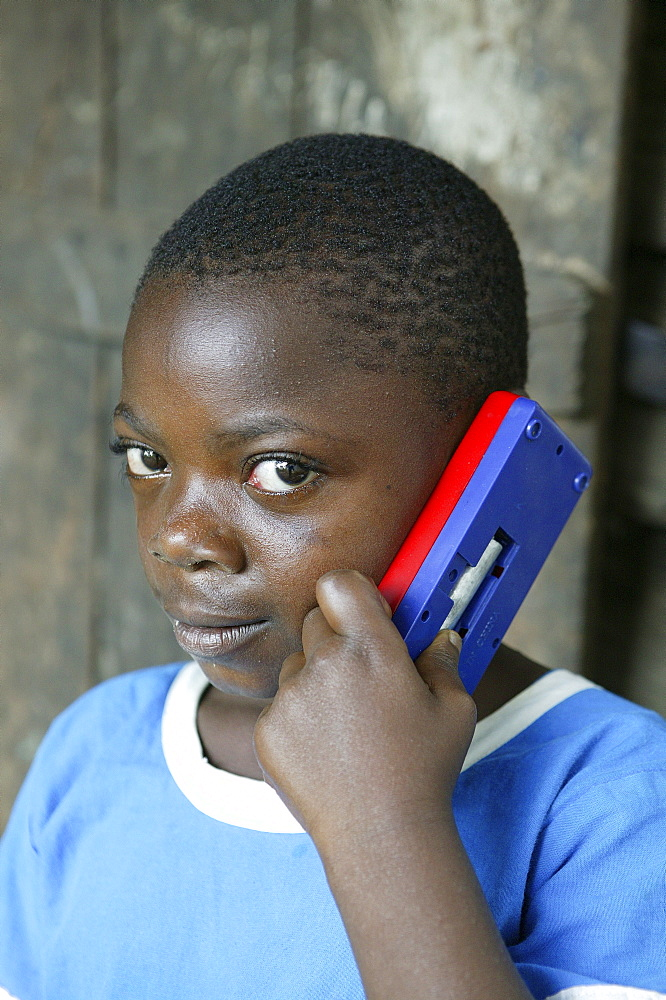 Boy holding a toy mobile phone to his ear, Cameroon, Africa