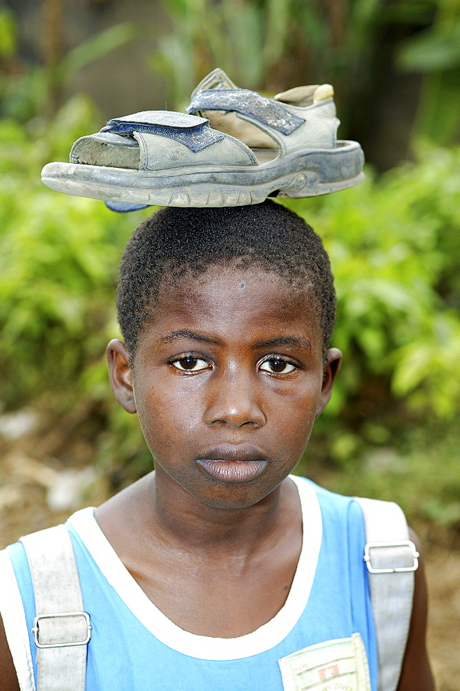 Boy balancing a shoe on his head, Cameroon, Africa