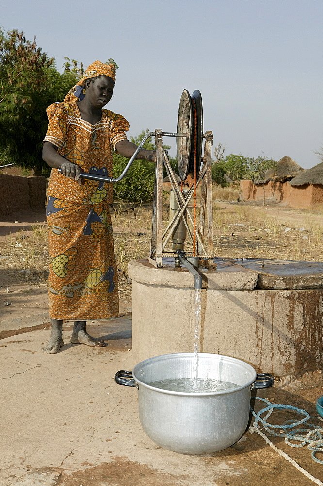 Woman getting water from a wheeled well, Pakete, Cameroon, Africa