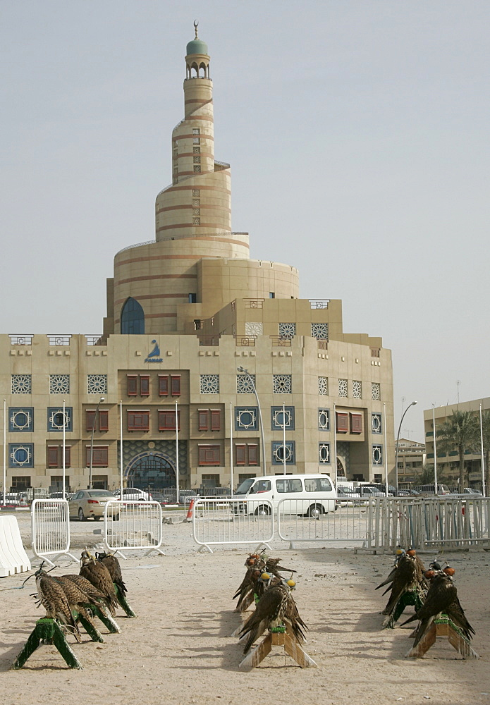 Qatar, Doha, the big tower of the FANAR (Qatar Islamic Cultural Center) building, Arabian architecture, in the foreground falcons are sitting in front of a falconer's shop