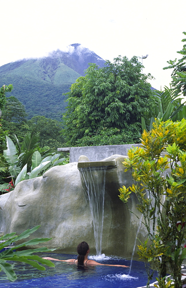 A woman is relaxing in a Thermal bath close to the volcano Arenal, La Fortuna, Costa Rica, Central America