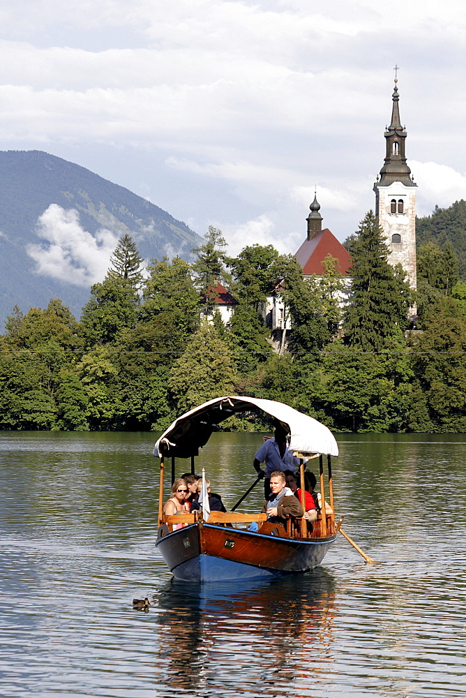Excursion boat on Lake Bled in front of Assumption of Mary's Pilgrimage Church, Bled, Slovenia