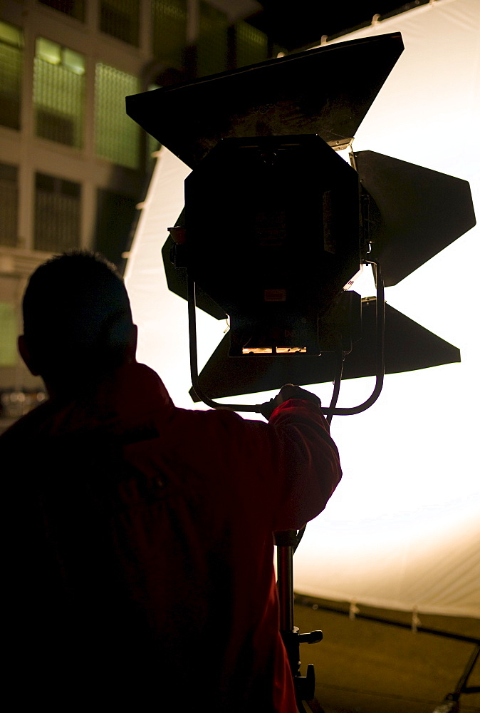 Lighting technician setting up a floodlight on a film set in Germany, Europe