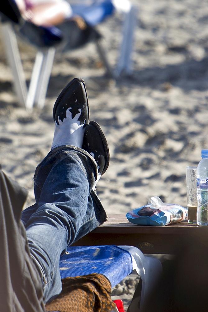 Man with Cowboy boots at Les Salinas beach, Ibiza, Balearen, Spanien