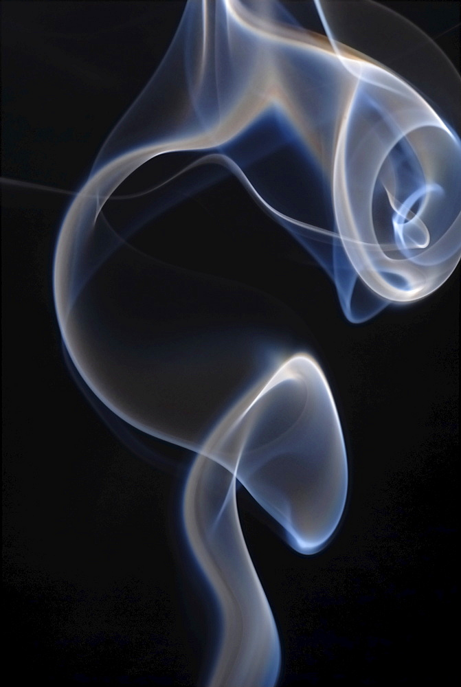 Smoke rising from an incense stick in backlight