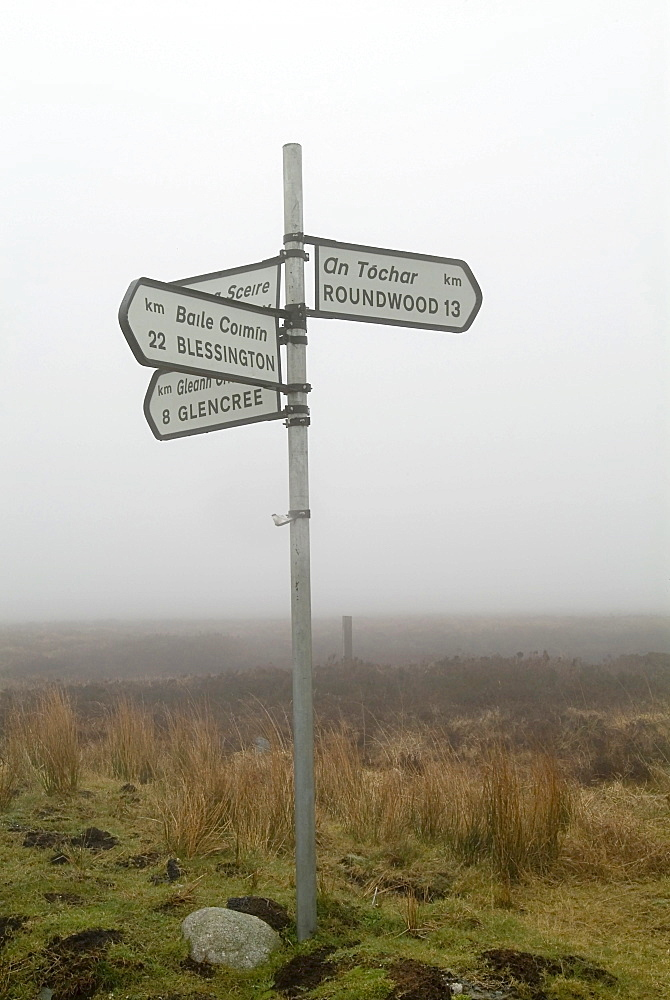 Directional signpost, signs written in English and Gaelic, Wicklow Mountains, County Wicklow, Ireland