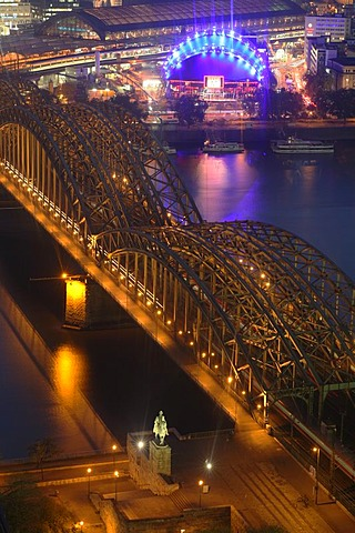 """Illuminated city center with Hohenzollern bridge, central train station and """"Rock Me"""" tent, Cologne, NRW, Germany"""