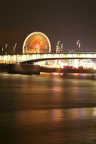 Deutzer bridge over the Rhine river and fair lights with the big wheel in Cologne, NRW, Germany