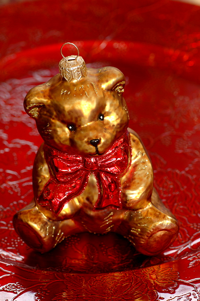 Bear with red bow, Christmas ornament sitting on red plate