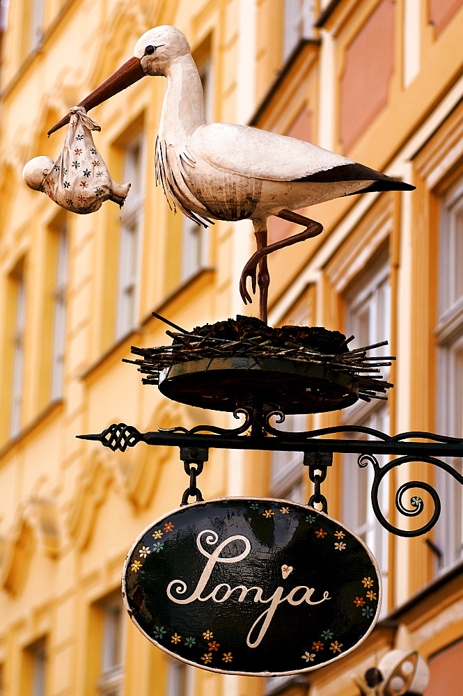 Sculpture of a stock holding a baby in front of a children's clothing shop, Bamberg, Upper Franconia, Bavaria, Germany