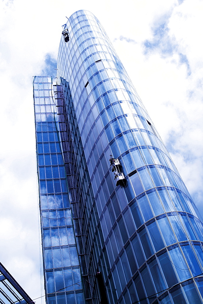 Window-cleaner cleaning the glass facade of a high-rise building, exterior