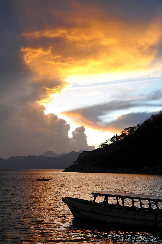 Sunset, back light, dramatic clouds, boat, Lake Atitlan, Guatemala, Central America