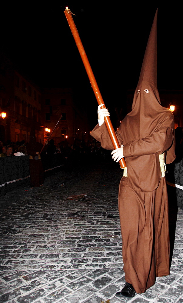 Penitent dressed in brown penitential robe (nazareno) carrying large candle at night, Semana Santa, Holy Week Procession, Huelva, Andalusia, Spain
