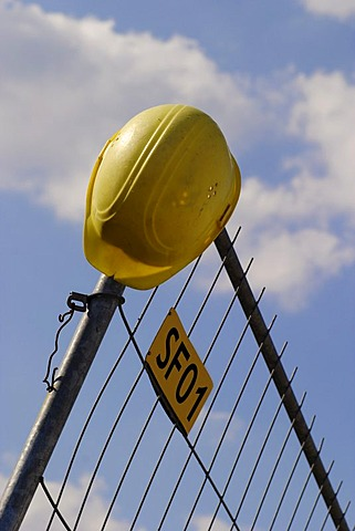 Yellow hardhat set on building site fence, Stuttgart, Germany, Europe
