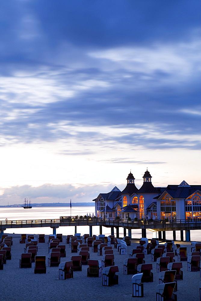 Pier behind rows of roofed wicker beach chairs, dusk, Sellin, Ruegen, Baltic Sea, Mecklenburg-Western Pomerania, Germany, Europe