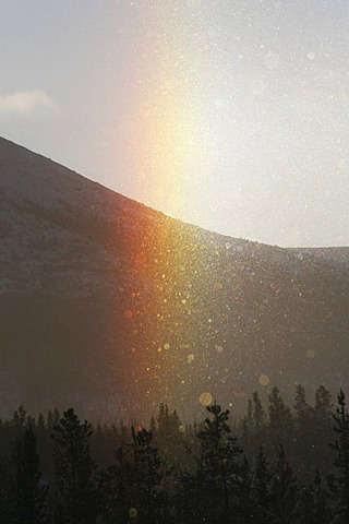 Sundog appearing in ice fog, rainbow colours, ice crystals, Yukon Territory, Canada