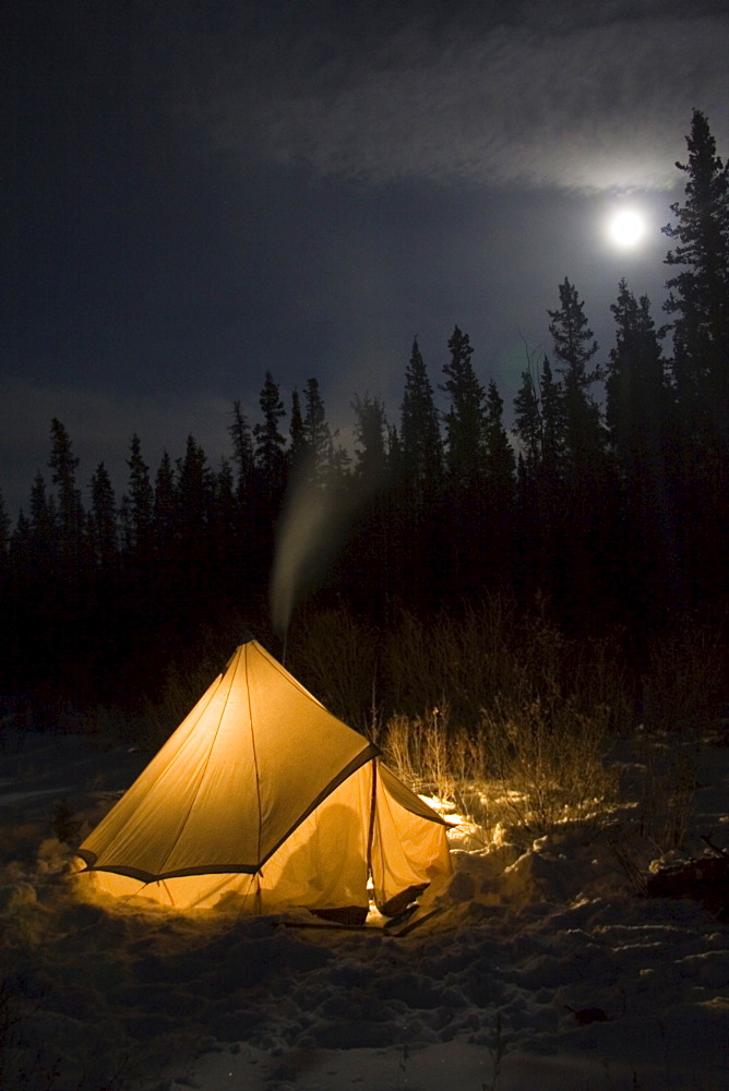 Illuminated tent with smoke coming out of a stove pipe, moon, Yukon Territory, Canada, North America