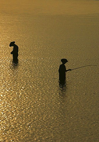 Silhouettes of fishermen standing in the water at sunset