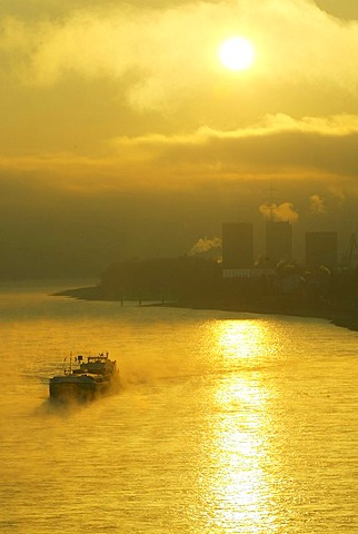 A freighter in the sunrise on the rhine near Bendorf, Rhineland-Palatinate, Germany