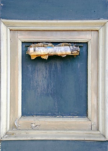 Old newspaper in a letter slot of a frontdoor