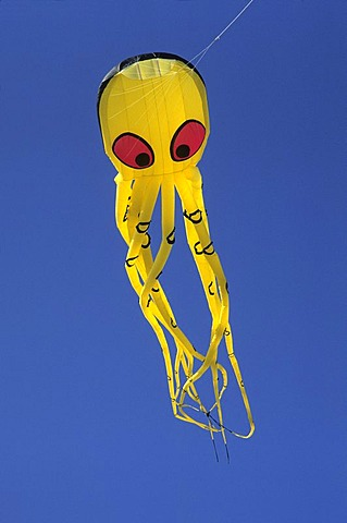 Yellow Kite in shape of an octopus with red eyes in the air