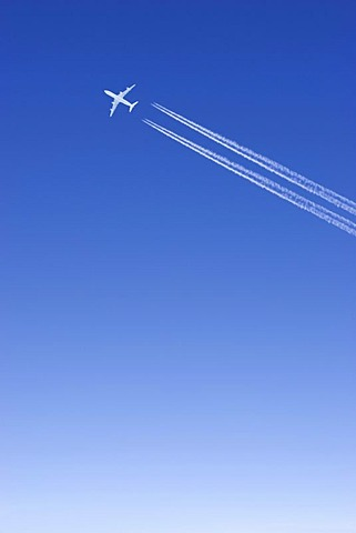 One single passenger jet with condensation trail white in blue sky