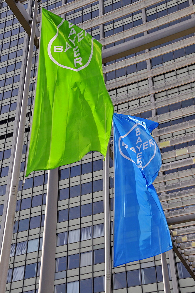Blue and green flags of the Bayer corporation visible against a high-rise office building at their headquarters in Leverkusen, North Rhine-Westphalia, Germany, Europe