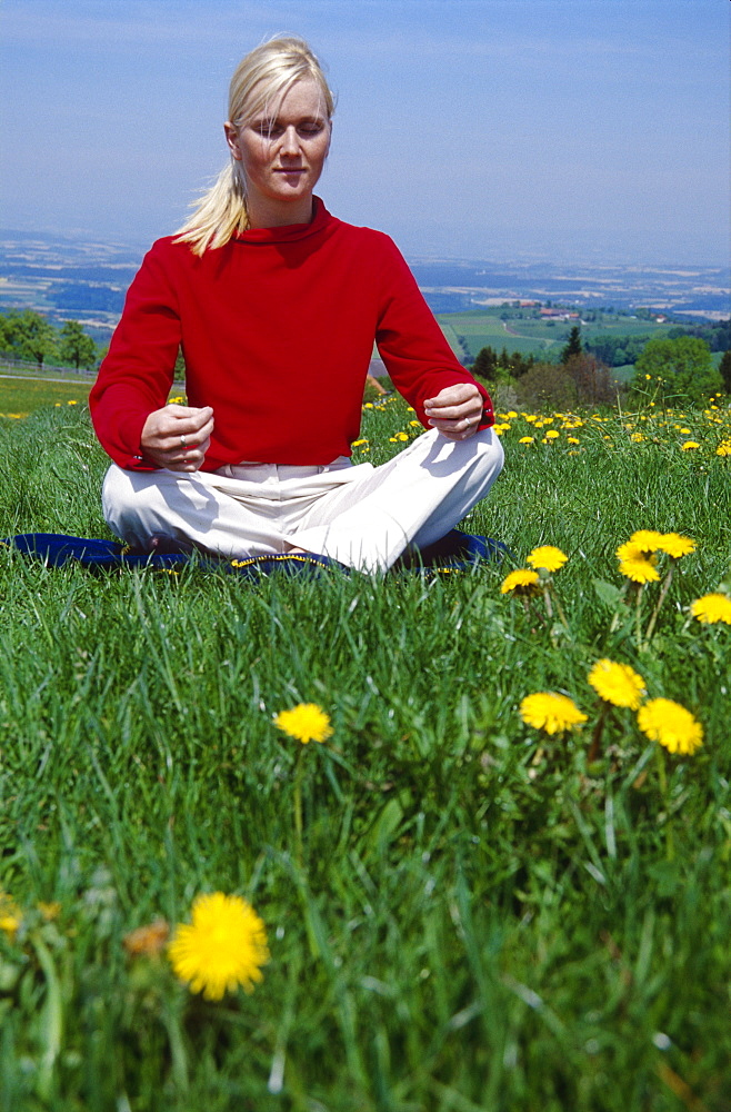 Blond woman wearing a red pullover sitting on a meadow and meditating