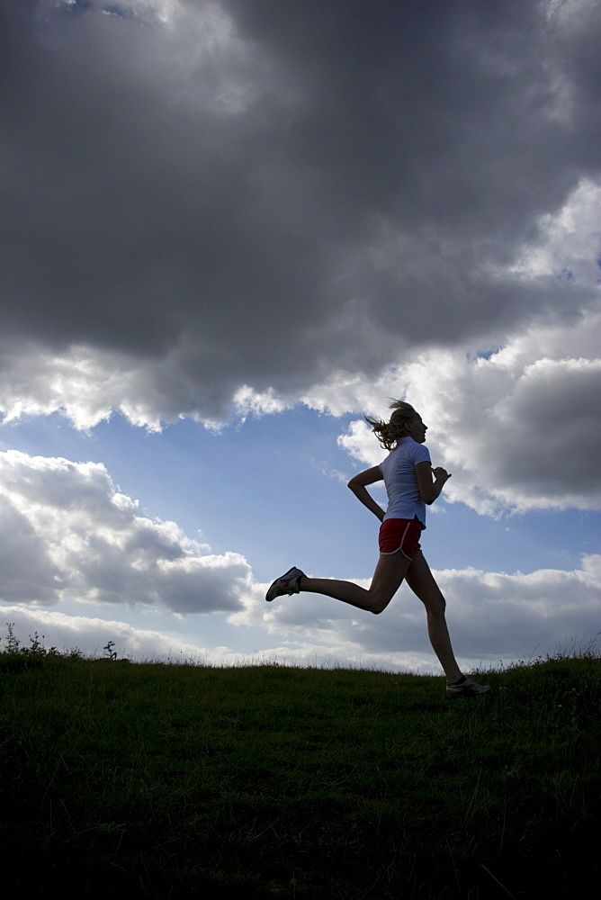 Running woman as a silhouette in front of a sky with dark clouds