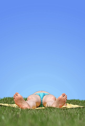 Man wearing a swimsuit lying on his back while sunbathing on a meadow