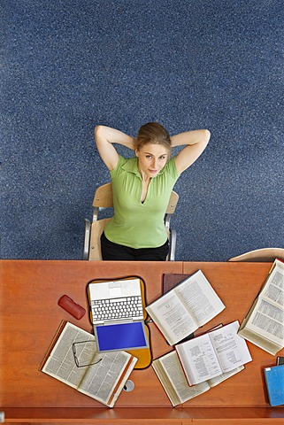 Female student sitting at a desk with a laptop and books, top view