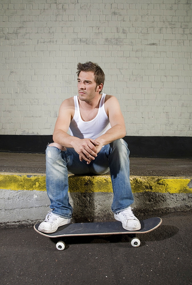 Skateboarder sitting on a loading ramp, relaxed