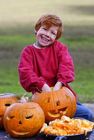 Boy carving a jack-o-lantern from a pumpkin for Halloween