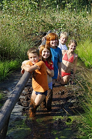Children smeared with mud, mud bath in the Sterntaler Filze, moorland, peat fields in Bad Feilnbach, Upper Bavaria, Bavaria, Germany, Europe