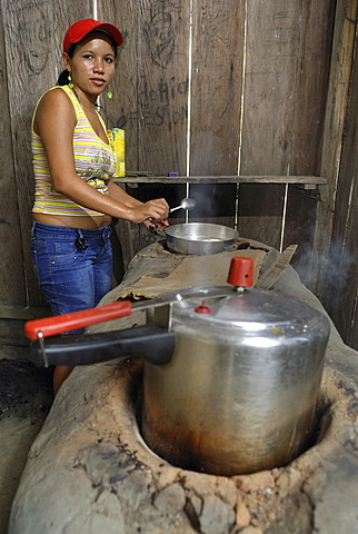 Woman cooking in simple kitchen, Amazon Basin, Brazil