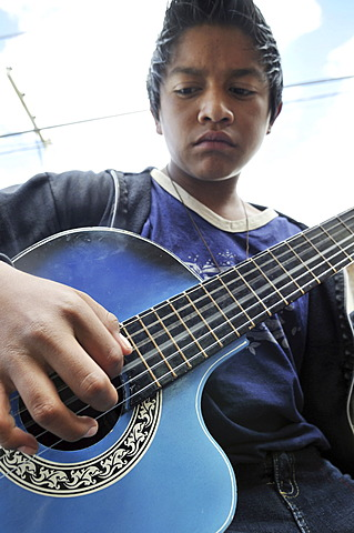 Teenager, 14 years old, practising on a guitar, slums of Cerro Norte, Bogotá, Columbia