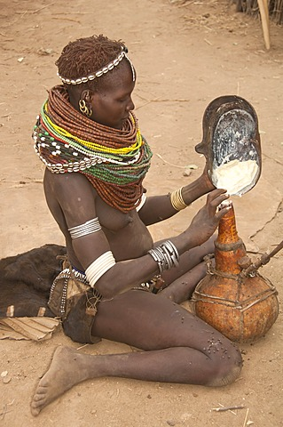 Nyangatom, Bume or Buma woman pouring sorghum in a calabash, Omo Valley, Ethiopia, Africa
