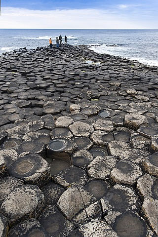 Tourists standing on headland on basaltic rocks, Giant's Causeway, Coleraine, Northern Ireland, United Kingdom, Europe