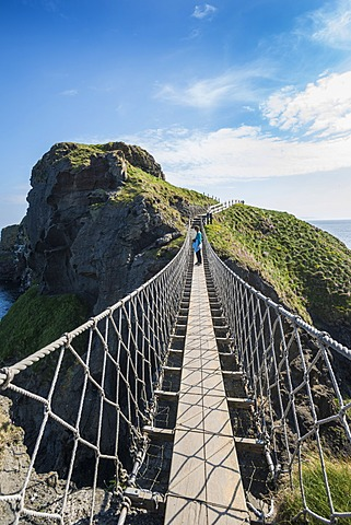 Carrick-a-Rede Bridge, woman standing on the suspension bridge, Moyle, Northern Ireland, United Kingdom, Europe