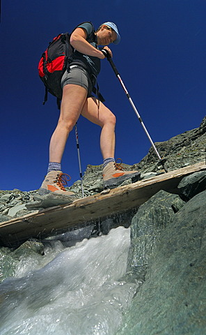 Hiker crossing a wooden bridge above a mountain brook, National Park Hohe Tauern, Tyrol, Austria