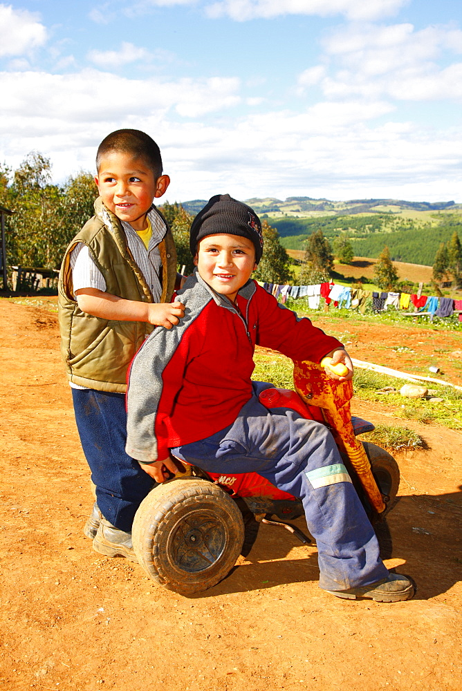 Two boys with a tricycle, Mapuche Indians, near Concepción, Southern Chile, Chile, South America