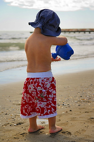 Little boy on the beach playing with a watering can, Caorle, Veneto, Italy