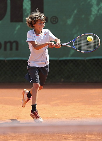Boy, 10, playing tennis, hitting with a two-handed backhand, Munich, Upper Bavaria, Bavaria, Germany
