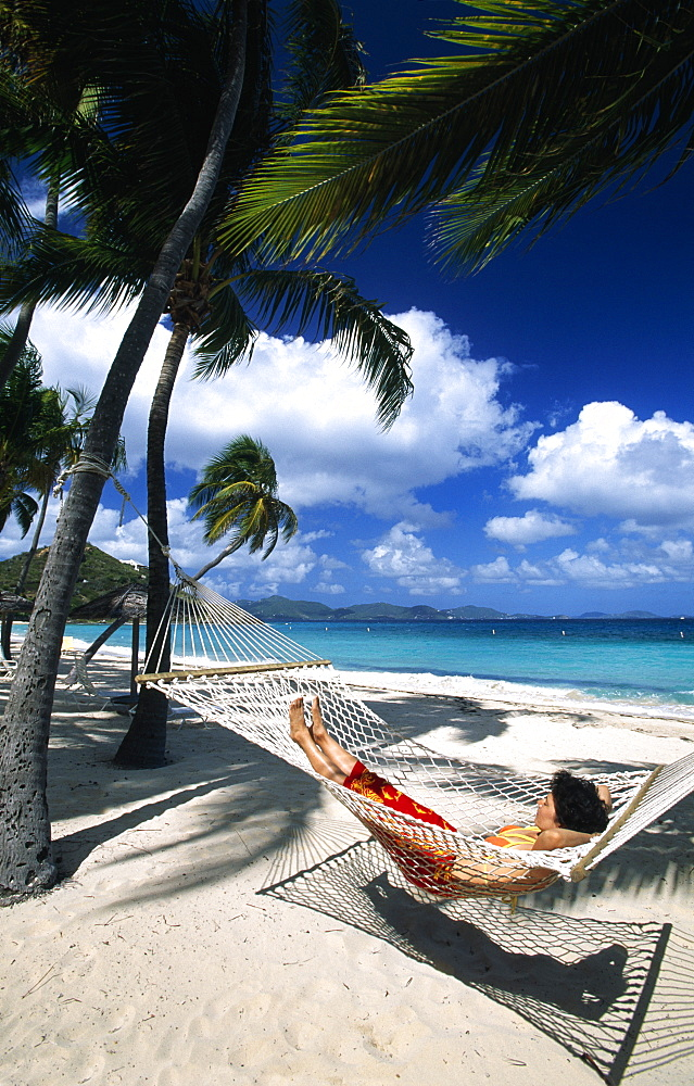 Woman in a hammock under palm trees on a beach on Peter Island, British Virgin Islands, Caribbean