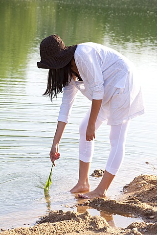 Young woman wearing a straw hat on the beach of a quarry pond