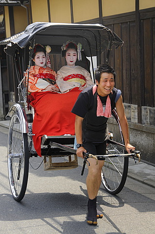Maikos, apprentice Geishas, being pulled by a rickshaw driver through the historic city centre of Kyoto, Japan, Asia