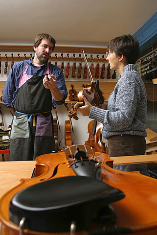 Violin-maker (luthier) with a customer in his shop