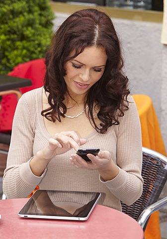 Young woman using an iPhone mobile telephone and an iPad tablet computer in a sidewalk cafe