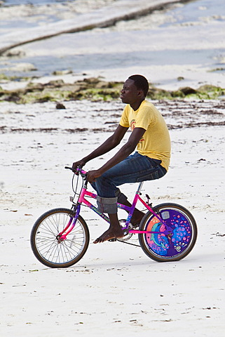 Bicycle rider on the beach at Pingwe, Zanzibar, Tanzania, Africa