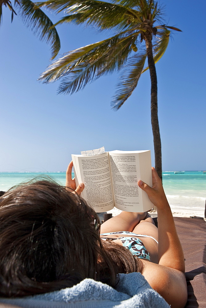 Young woman on a beach reading a book under palm trees
